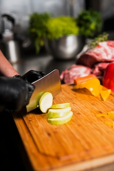 Cook cutting zucchini on board