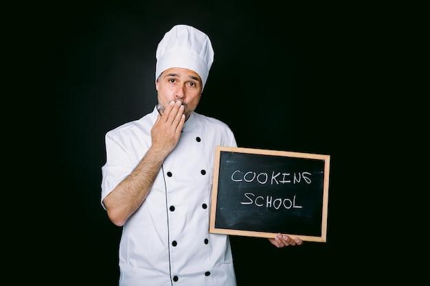 재킷과 흰색 모자를 쓴 요리사는 손을 입에 대고 다음과 같은 칠판을 들고 있습니다. 검정색 배경에 요리 학교. 레스토랑, 음식 및 요리 학교 개념입니다.