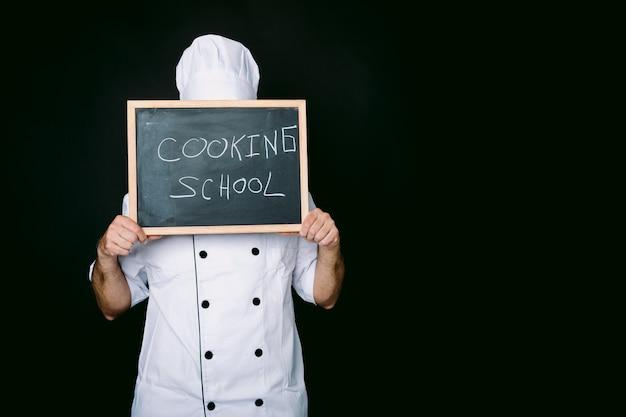 흰색 모자와 재킷을 입은 쿡은 칠판으로 얼굴을 가립니다. 검정색 배경에 요리 학교. 레스토랑, 음식 및 요리 학교 개념입니다.