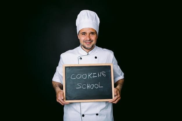흰색 모자와 재킷을 입은 요리사는 검정색 배경에 요리 학교라고 적힌 칠판을 들고 있습니다. 레스토랑, 음식 및 요리 학교 개념입니다.