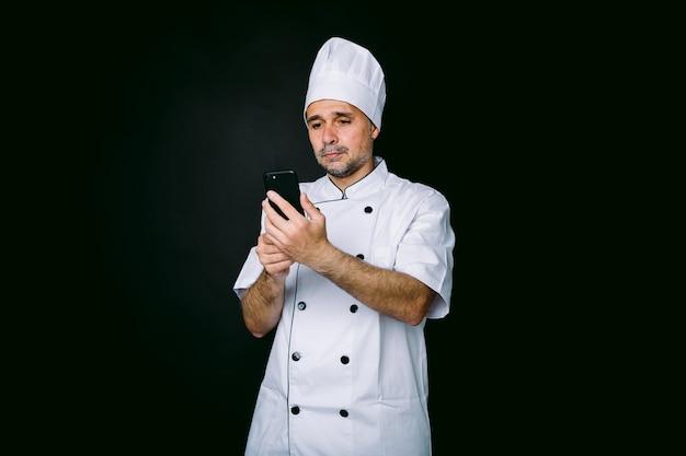 흰색 모자와 재킷을 입은 쿡은 검은색 바탕에 휴대폰을 보고 있습니다. 레스토랑, 음식 및 테이크아웃 컨셉입니다.