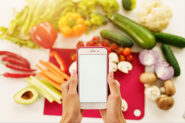 Cook follows a recipe of vegetables from the smartphone