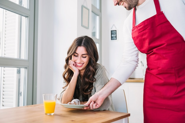Cook giving croissant to girlfriend