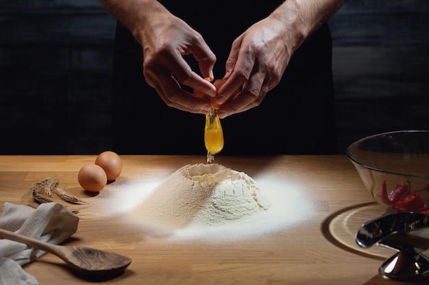 Cook hands kneading dough, cracking an egg in flour