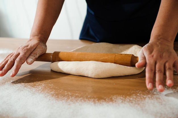 Cook hands kneading dough, sprinkling piece of dough with white wheat flour.
