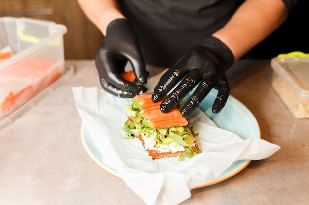 Cook hands preparing and making sandwich.