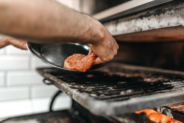 요리사 손은 그릴 오븐에 고기를 넣고 햄버거를 요리합니다. 햄버거 준비 과정, 패스트 푸드, 바베큐