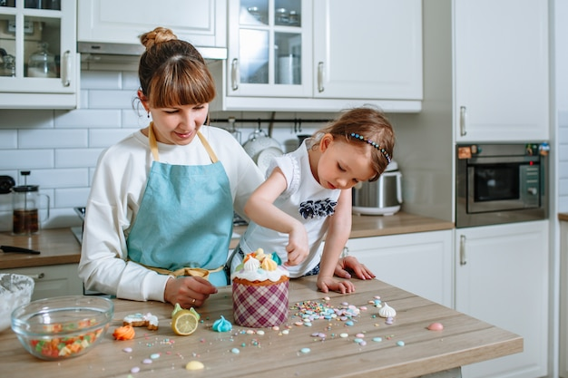 The cook and her daughter lay out sweet figures on the icing of the easter cake