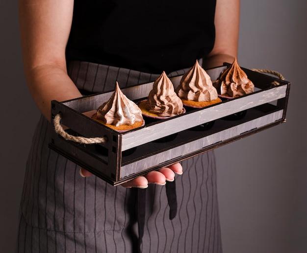 カップケーキとアイシングでトレイを保持しているクック