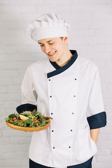 Cook holding wooden plate with salad
