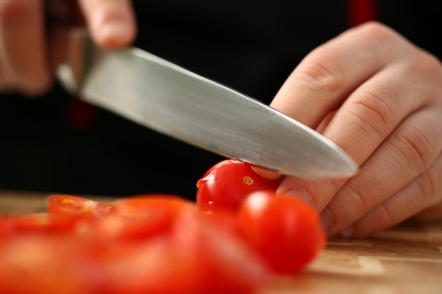 Повар держит нож в руке и режет