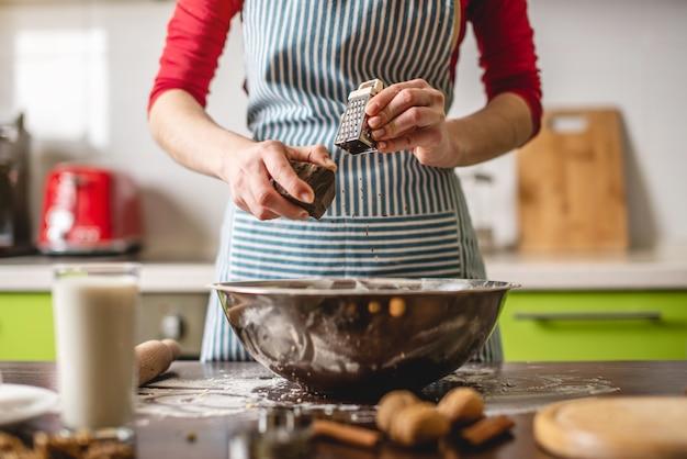 カラフルなキッチンで自宅でクッキーを作る主婦を調理する