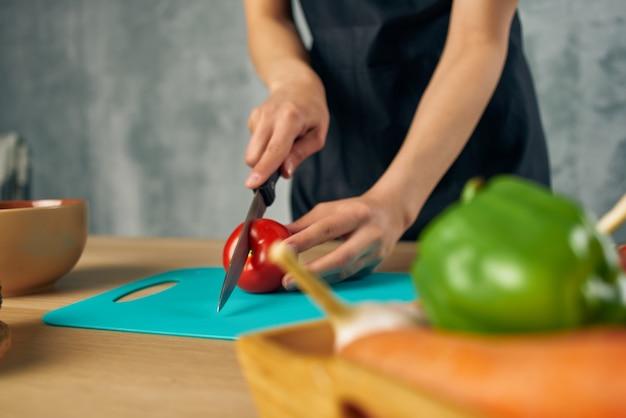 健康的なまな板を調理する黒いエプロンで調理する