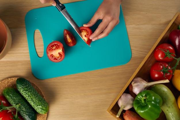 野菜サラダダイエットを切るキッチンで黒いエプロンで調理する