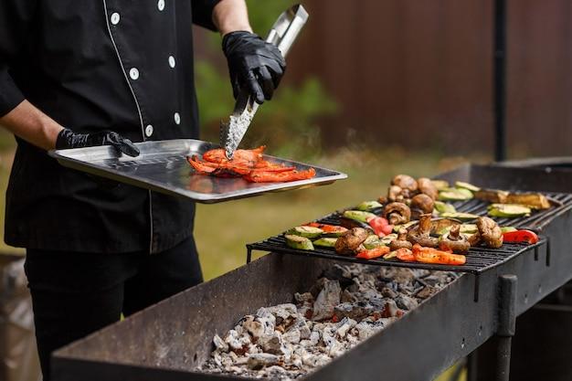 Готовьте в черном костюме, снимите с решеток острый перец много овощей лежит на гриле кейтеринг