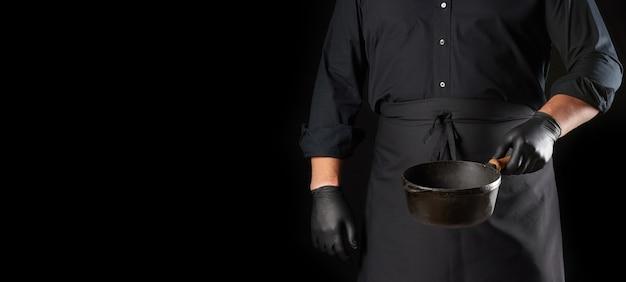 Повар в черной униформе и перчатках держит пустую круглую винтажную чугунную сковороду