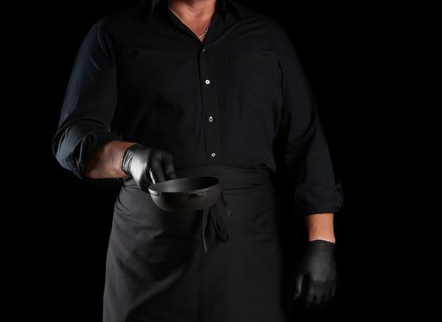 黒のユニフォームで調理し、ラテックスの手袋は空の丸いヴィンテージ黒鋳鉄鍋を保持しています