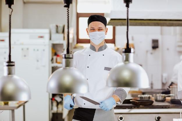 Повар в белой форме, медицинских перчатках и маске позирует с ножами на кухне возле распределительного стола с лампами.