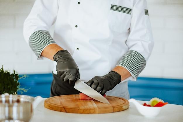 Повар в белой форме с черными медицинскими перчатками нарезает филе рыбы на кухне.
