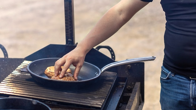 요리사는 그릴에 프라이팬에 튀김 햄버거 빵을 만지고 있습니다. 바베큐. 길거리 음식