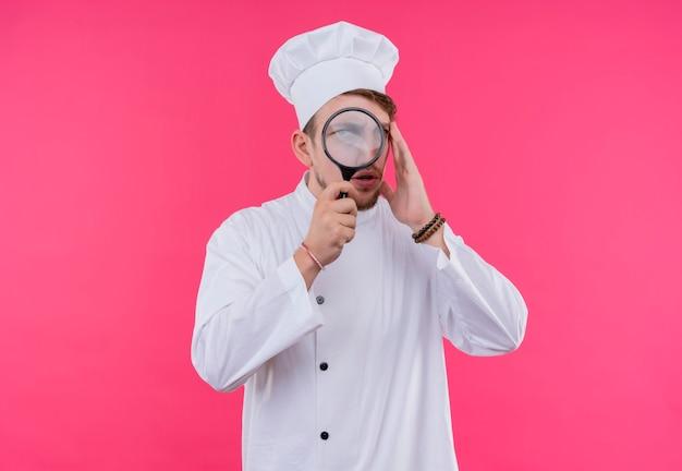 ピンクの壁の上に立っている拡大鏡からカメラを見て料理人