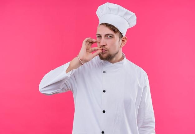 ピンクの壁の上に立っておいしいジェスチャーを作るカメラを見て料理人
