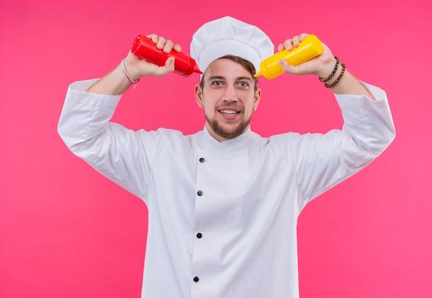 ピンクの壁の上に立っている赤と黄色のボトルで指しているカメラを見て料理人