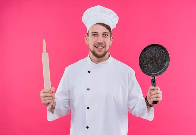 ピンクの壁の上に立っているめん棒と鍋で顔にカメラの笑顔を見ながら料理人