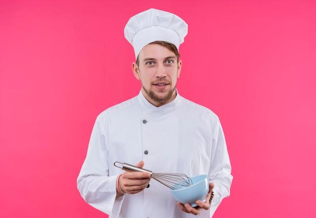 ピンクの壁の上に立っているボウルに泡立て器で顔にカメラの笑顔を見て料理人