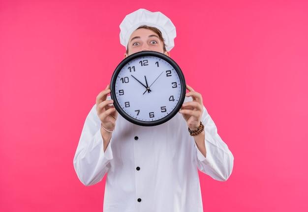 ピンクの壁の上に立っている時計を示す顔にカメラの驚きを見て料理人