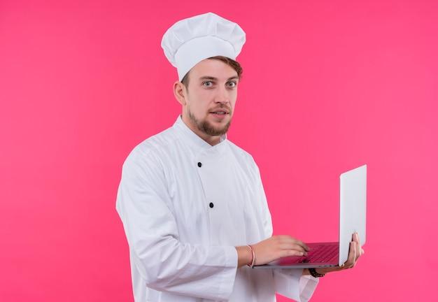 분홍색 벽 위에 서있는 손에 노트북으로 얼굴에 카메라 놀람을보고 요리