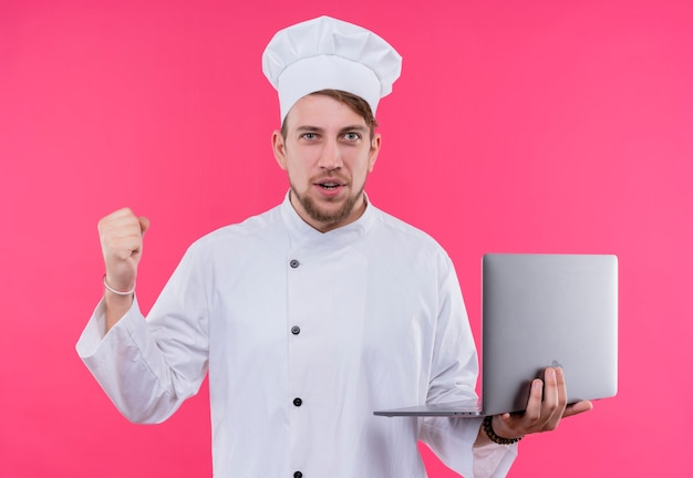 ピンクの壁の上に立っている手にノートを持って顔のカメラの勝利の表情を見て料理人