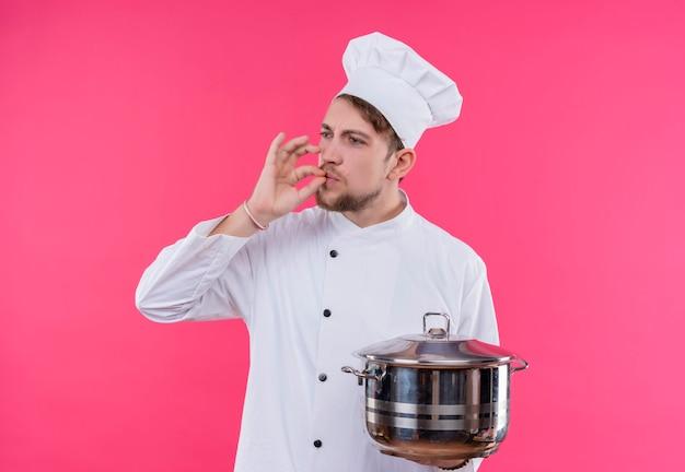 ピンクの壁の上に立っている手に鍋でおいしいジェスチャーを作って目をそらして料理