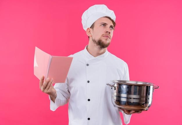 ピンクの壁の上に立っているコピーブックとパンで顔に物思いにふける目をそらして料理する