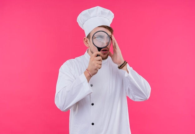 Cook looking at camera from magnifier standing over pink wall