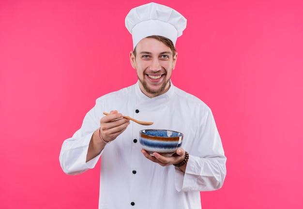 Cucinare guardando il sorriso della fotocamera sul viso gustando qualcosa dalla ciotola in piedi sul muro rosa