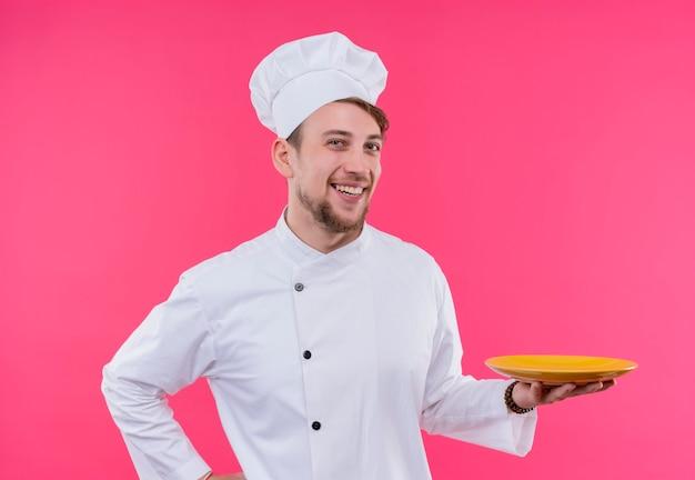 Cucinare guardando il sorriso della fotocamera sul viso con piatto a portata di mano in piedi sopra il muro rosa