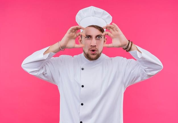 Cuocere guardando la sorpresa della fotocamera sul viso che fa piccolo gesto in piedi sopra il muro rosa