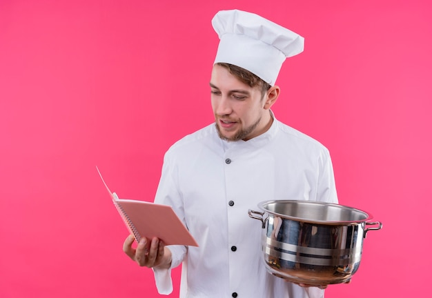 ピンクの壁の上に立っている鍋で顔に笑顔をコピーブックを探して料理人