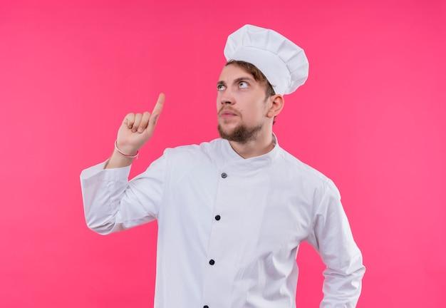ピンクの壁の上に立って上向きに見上げる料理人