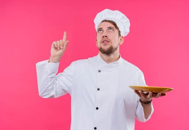 ピンクの壁の上に立っている一方でプレートで上向きに見上げる料理人