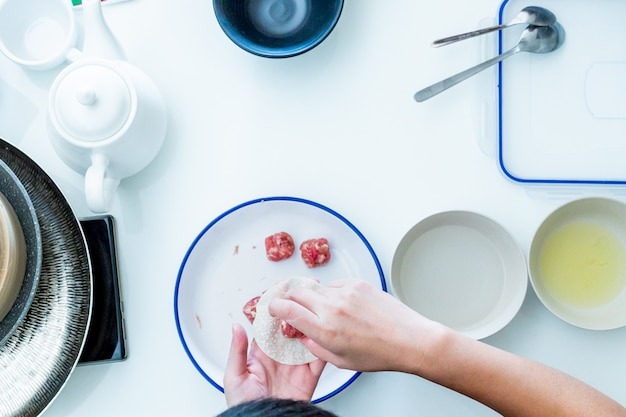 The cook makes dumplings at hand from the above view. flat lay kitchenware.