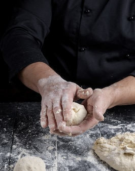 Cook making dough balls on a black wooden table