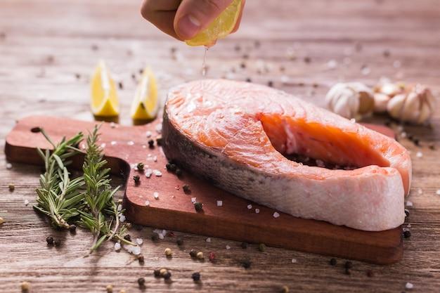 Человек-повар покрывает стейк из лосося и выжимает лимонный сок