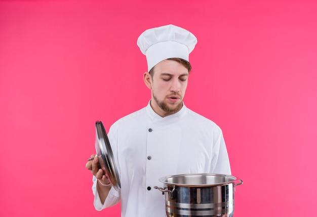 Cuocere aprendo la padella con lo shock sul viso in piedi sopra il muro rosa
