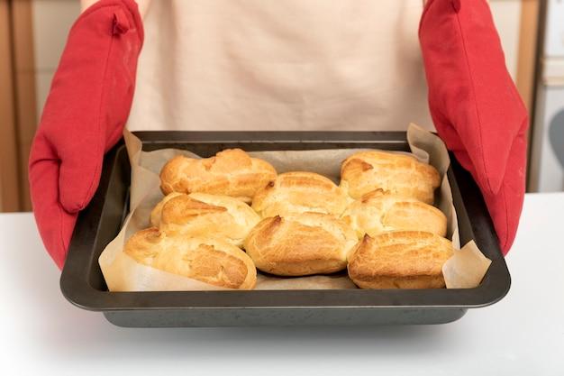 Cook in oven mitt holds baking sheet of scones