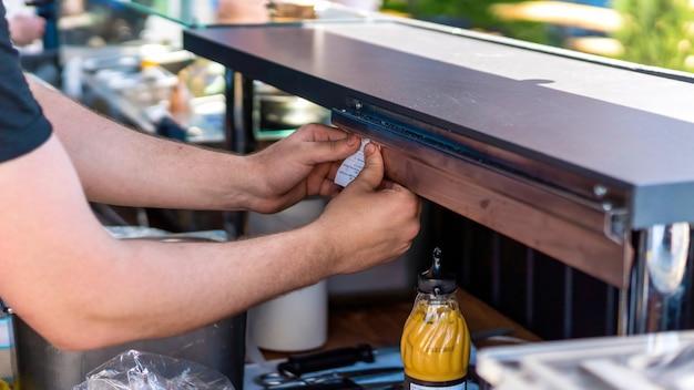 작업장 바베큐장 위에 주문서를 꽂고 있는 쿡. 길거리 음식 프리미엄 사진
