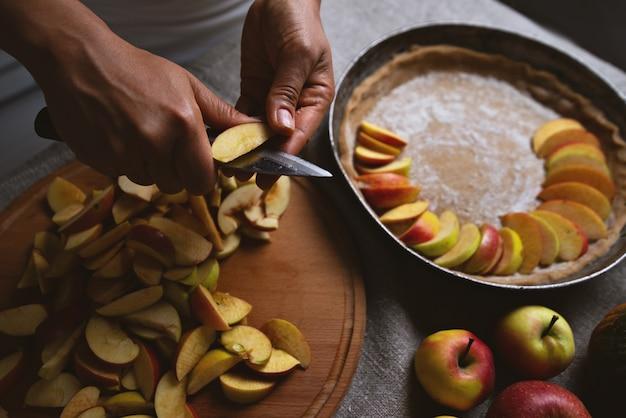 クックは生地の表面にリンゴを置きます