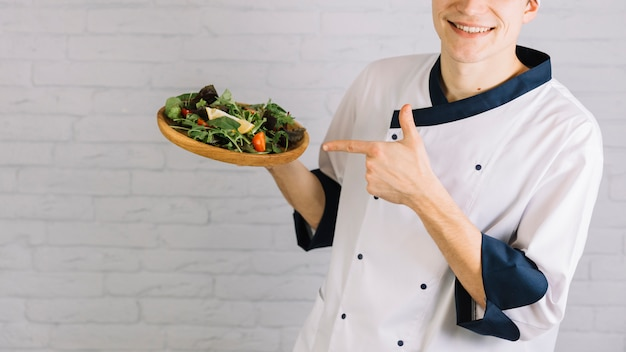 Cook pointing finger at fresh salad on wooden plate