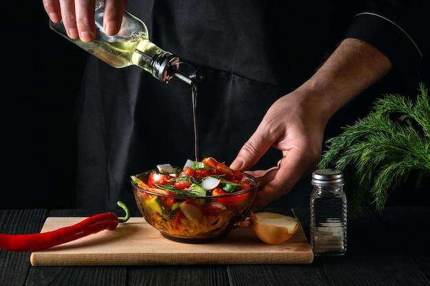 クックはサラダのボウルにオリーブオイルを注ぎます